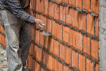 Builder worker, clay block wall and trowel