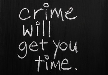 Crime Will Get You Time written on a blackboard