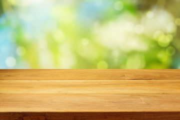Empty wooden deck table over garden bokeh background