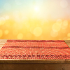 Bamboo tablecloth on wooden table over sunser bokeh  background.