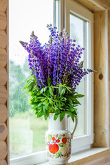 Bouquet of lupine flowers in a vase on the windowsill