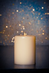 candle with flame on wood table on blue bokeh background