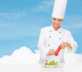 smiling female chef with preparing salad