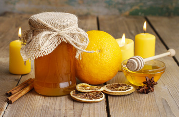 Jar of honey, oranges and candles on wooden table