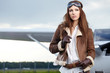 Portrait of young beautiful woman pilot in front of airplane. - 66312147