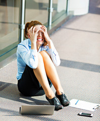 Stressed, crying business woman sitting on a floor