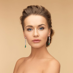 woman with diamond and emerald earrings