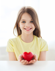 smiling little girl with red heart at home