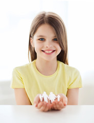 smiling little girl showing paper man family