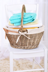 Colorful towels in basket on chair, on light background