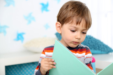 Cute little boy reading book in room
