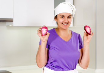Smiling chef holding up a sliced red onion