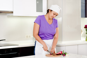 Cook chopping fresh vegetables in the kitchen