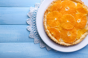 Homemade orange tart on plate, on color wooden background