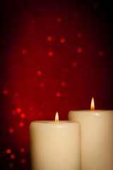 candles with flame and space for text on red bokeh