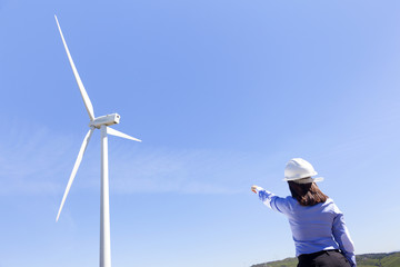 Female engineer pointing to windmill at wind farm