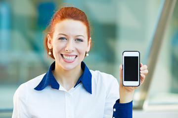 Happy, smiling woman showing her smart phone