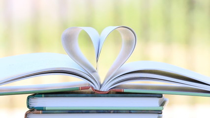 Book stack open page heart shape in wind