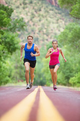 Sprinting running couple on road exercising sport