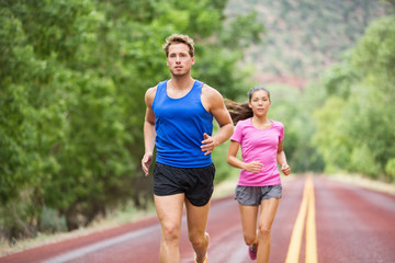 Runners - couple running training marathon on road
