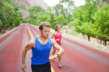 Sport - couple running exercising using watch