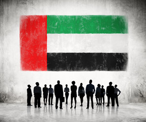 Silhouettes of Business People Looking at the Flag of UAE