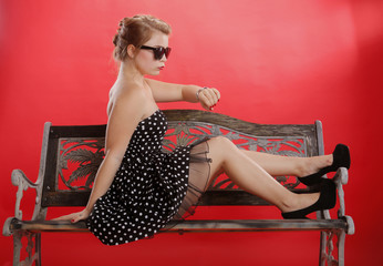 Young woman waits on a retro bench
