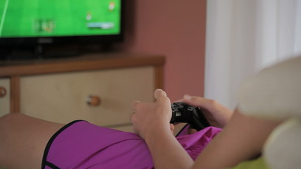 Teen playing with game at home (back view)