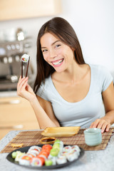 Sushi chopstick holding young smiling Asian female