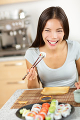 Woman eating sushi maki holding chopsticks