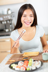 Sushi eating young Asian woman - smiling happily