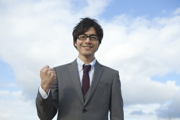 メガネを掛けてガッツポーズをするビジネスマン