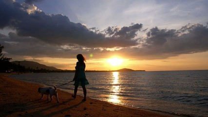Young Woman and her Cute Dog Walking on the Beach at Beautiful