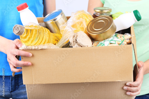 Volunteers with donation box with foodstuffs on grey background - 66319117