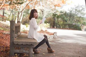 秋の紅葉した公園のベンチで読書をする女性