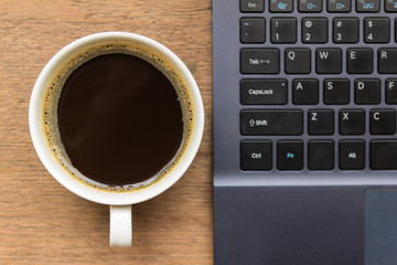 Top view of coffee cup , laptop on wooden table
