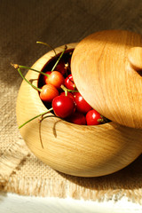 Sweet cherries in bowl on wooden table