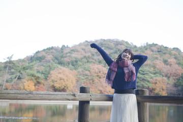 秋の紅葉の公園の池のほとりで伸びをする女性