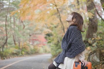 秋の紅葉した公園でトランクに座っている女性