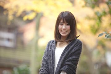 秋の紅葉した公園で立っている笑顔の女性