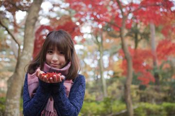 秋の紅葉の公園で落ち葉を手のひらに乗せる笑顔の女性