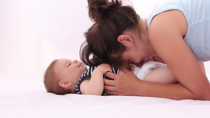 Mother tickling her little baby boy against white background