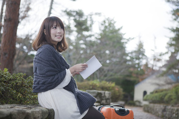 秋の石畳にトランクを置いて本を読む笑顔の女性