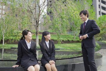 ベンチに座って会話をするビジネスウーマンとビジネスマン