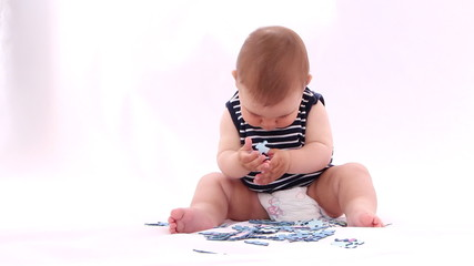 Baby boy playing with puzzle against white background