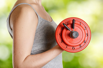 Beginner female athlete holding dumbbell with clock dial. Time f