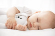 Carefree sleep little baby with a soft toy on the bed - 66325707