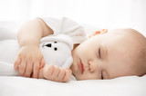 Fototapety Carefree sleep little baby with a soft toy on the bed