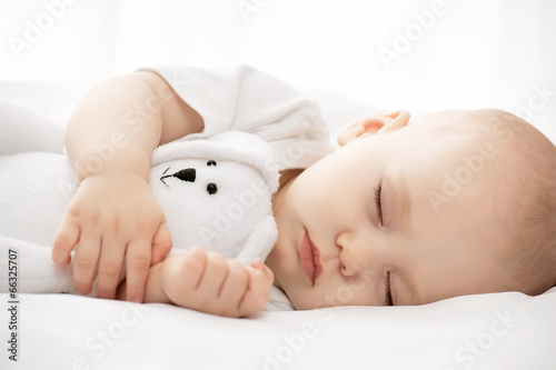 Leinwanddruck Bild Carefree sleep little baby with a soft toy on the bed