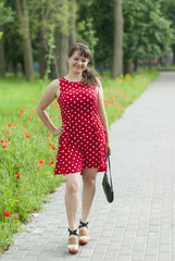 Young beautiful girl in a dress for a walk in the park.